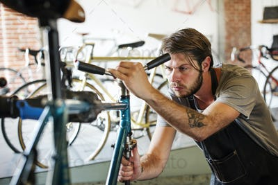 A man working in a bicycle repair shop, checking the frame of the bike.