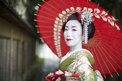 A woman dressed in the traeditional geisha style, holding a red paper parasol.