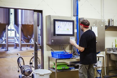 A brewer with a red bandana checking a computer monitor and testing the brewed beer.