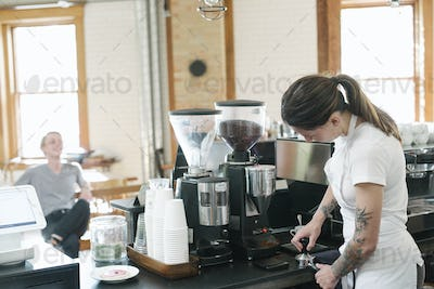 Woman wearing a white apron, standing in front of an espresso machine, holding a portafilter.