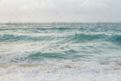 View of Pacific Ocean at dusk, waves and surf.
