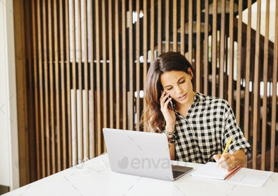 Woman working on a laptop computer, making phone call.
