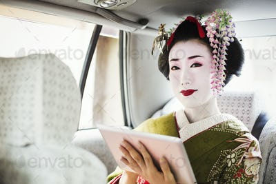 A traditional geisha wearing a kimono holding a digital tablet, travelling in a car.
