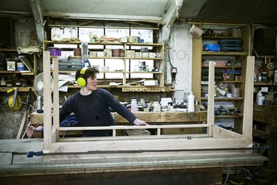 A woman working in a furniture maker's workshop, assembling a table.