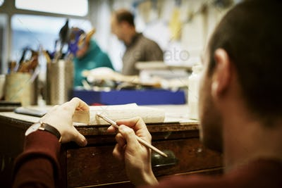 A man working on the bound pages of a book with a hand tool, to apply glue.