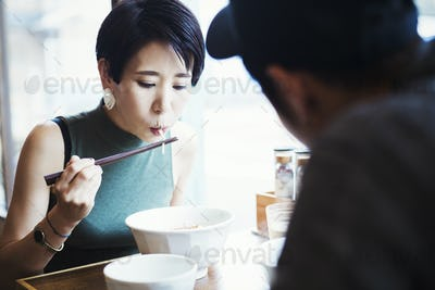 A ramen noodle cafe in a city.  A man and woman seated eating noodles from large white bowls.