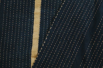 Close up of fabric with a black background and a grey stripe.