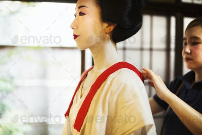 A geisha being dressed in traditional clothing with white face makeup.