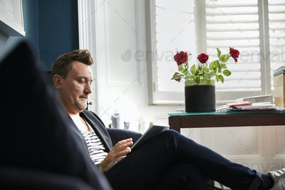 Man sitting in an office using his mobile phone, a vase with red roses on a desk.