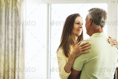 Senior couple standing indoors, embracing.