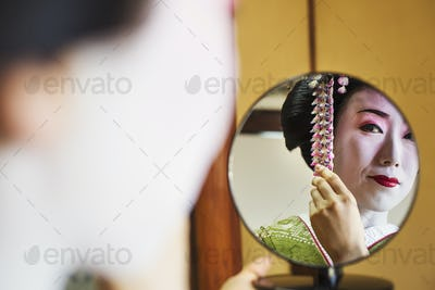 A woman wearing traditional geisha makeup and kimono, looking in a hand mirror.