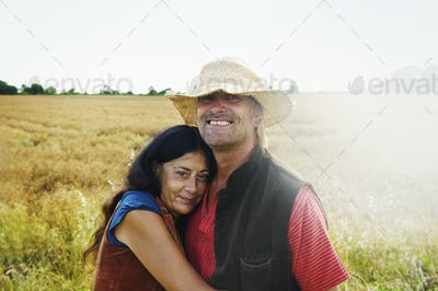 A man and woman holding hands in a field in summer.