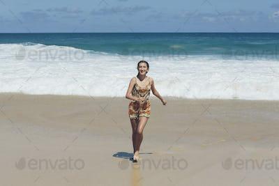 Happy thirteen year old running up the beach