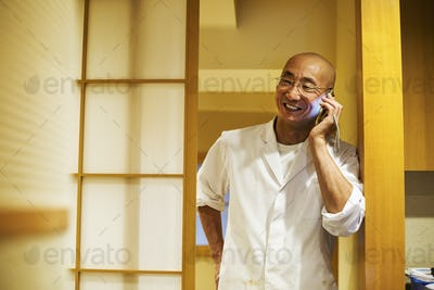 A chef  in a small commercial kitchen, an itamae or master chef on his smart phone.