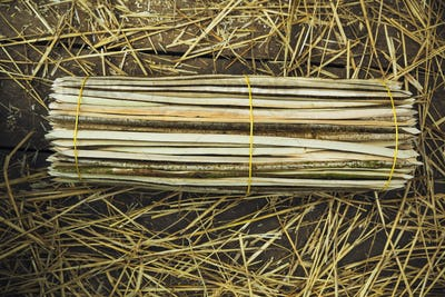 Close up of a bundle of wooden pegs used for thatching a roof.