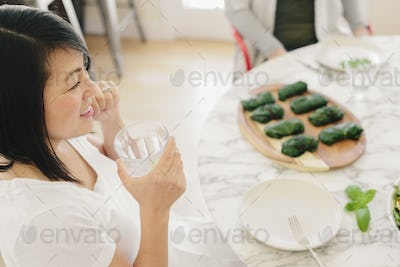 A woman seated at a table, by a plate of fresh dolmades.