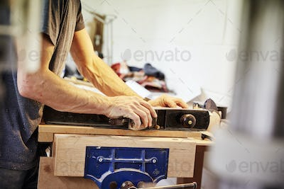 A man holding a piece of wood in a furniture workshop making bespoke contemporary furniture.