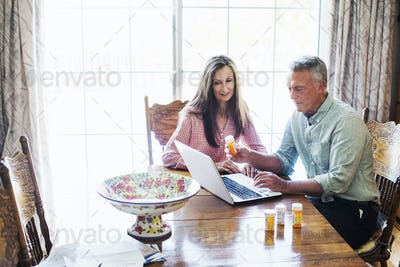 Senior couple sitting at a dining table, looking at a laptop computer.