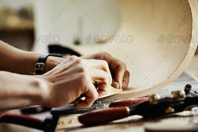 A man in a furniture workshop working on a piece of curved wood.
