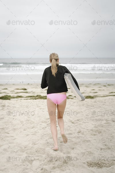 Rear view of a girl carrying a bodyboard, walking into the ocean.