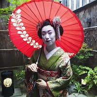 A geisha in costume holding an umbrella
