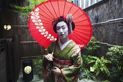 A geisha in costume holding an umbrella