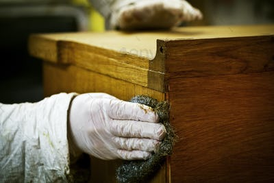 A person in gloves using wire wool to sand down or wax a piece of furniture.