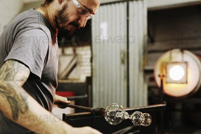A glassblower holding a blown glass on the end of a pipe, and shaping it.