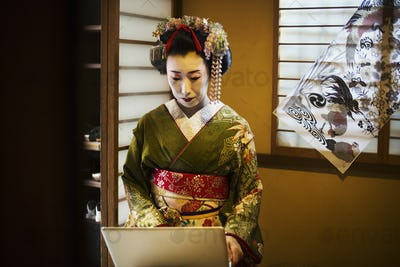 A woman dressed in the traditional geisha style using a laptop computer.