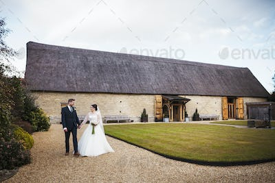 A bride and groom hand in hand, on their wedding day, in a garden.