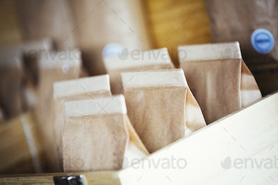 Specialist coffee shop. Bags of fresh ground coffee in a box on the counter.
