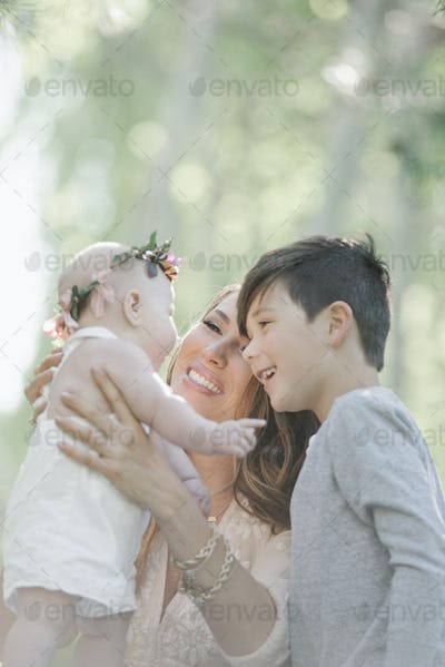 Portrait of a smiling mother, boy and baby girl with a flower wreath on her head.
