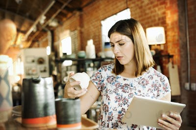 Young woman in a shop, holding a digital tablet and a ceramic mug.