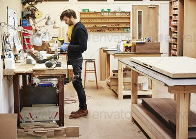 A man standing at a workbench holding and examining an object in a furniture workshop.