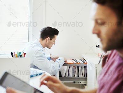 A man looking through files in an office, and a man using his digital tablet.