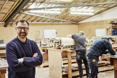 Three people in a furniture workshop making bespoke contemporary furniture pieces.
