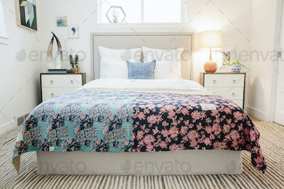 A bedroom in an apartment, with floral quilt