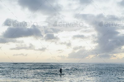 Man stand up paddling in calm waters at dusk