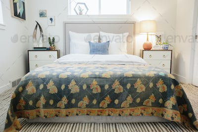 A bedroom in an apartment with a retro floral bedcover