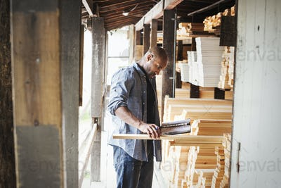 Man standing in a lumber yard, holding a folder, checking wood.