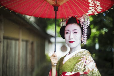 A woman in traditional geisha costume and make up