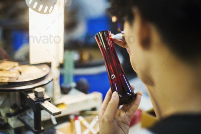 A craftsman in a glass maker's workshop inspecting a red glass vase and marking the exterior.