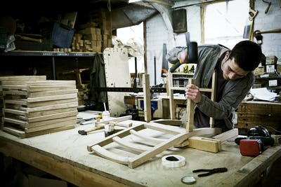 A man working in a furniture maker's workshop assembling a chair.