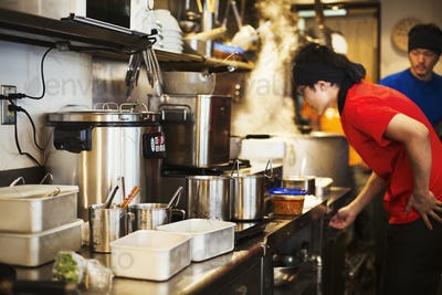 The ramen noodle shop.  Staff preparing food in a tiny kitchen