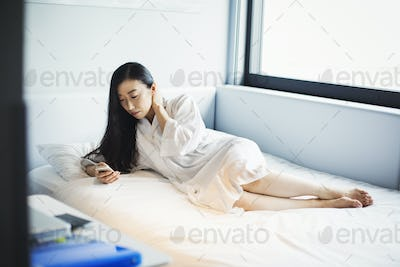 A woman in bed in a hotel, using her smart phone.