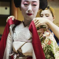 A woman being dressed as a geisha