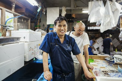 A traditional fresh fish market in Tokyo. Two men in aprons working on a fresh produce stall.