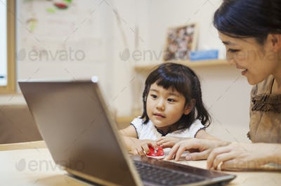 Family home. A woman and her daughter seated at a table looking at the screen of a laptop.