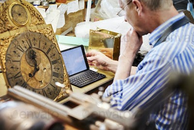 A clock maker in his workshop using a laptop. Antique clock face.