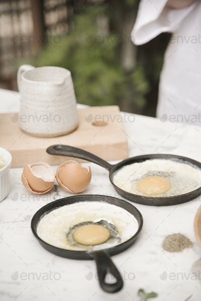 Two pans with fresh cracked eggs and a milk jug.